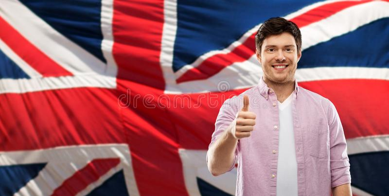 Happy man showing thumbs up over british flag. Gesture and people concept - happy young man showing thumbs up over british flag background royalty free stock photos