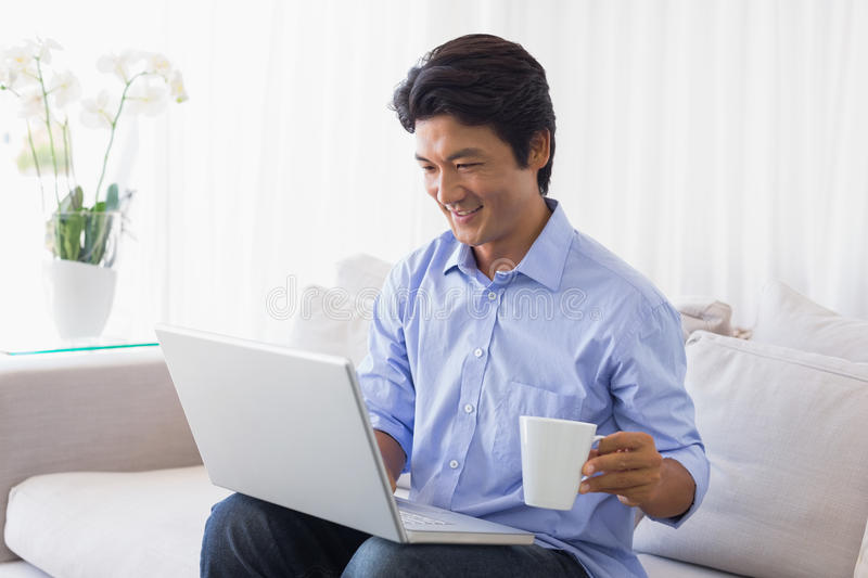 Happy man sitting on couch using laptop having coffee royalty free stock image