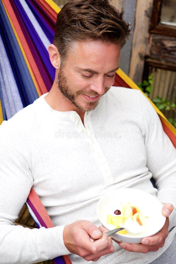 Happy man sitting in hammock eating fruit salad royalty free stock photo