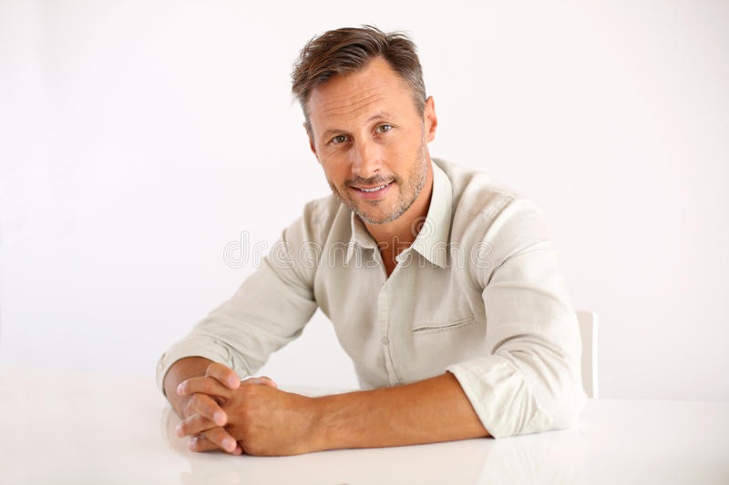 Happy man sitting with hands on table stock image