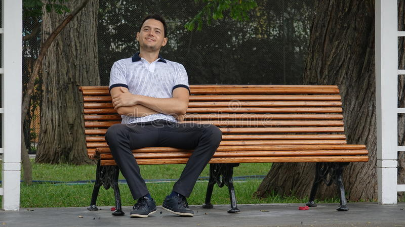 Happy Man Sitting On Park Bench royalty free stock images