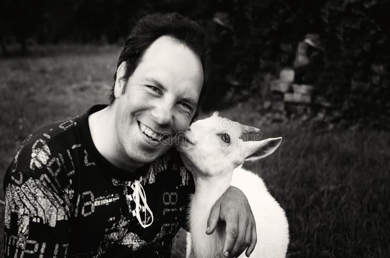 Happy man smiling with friendly goat stock photos