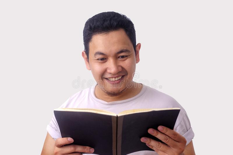 Happy Man Smiling While Reading Book royalty free stock photo