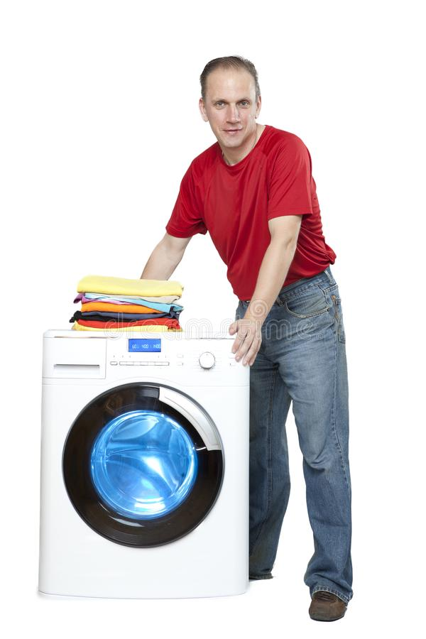 Happy man smiling standing next to a new washing machine stock image