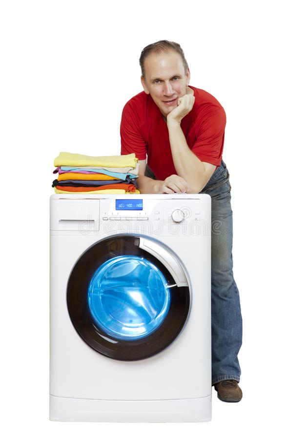 Happy man smiling standing next to a new washing machine and a stack of clean laundry stock photo