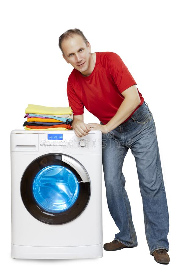 Happy man smiling standing next to a new washing machine and a stack of clean laundry stock photography