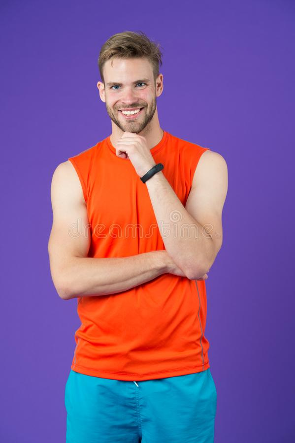 Happy man with sport smartwatch on violet background. Sportsman smile in orange vest and shorts. Fashion accessory for stock images