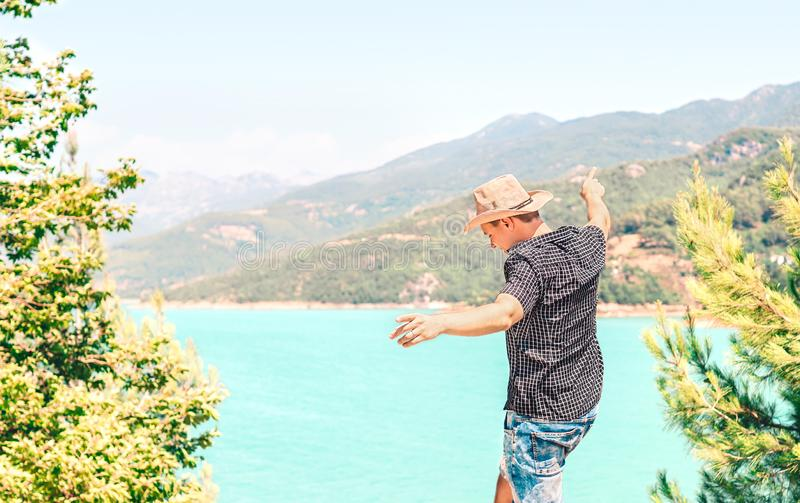 Happy man spreading arms and enjoying life in the mountain. Carefree guy with cowboy style hat feeling free. Journey to success. royalty free stock photography