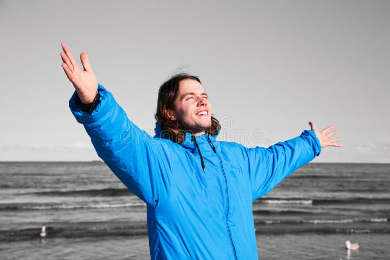 Happy man on the beach - b&w background. Overcoming depression. Happy man standing on the beach with hands up on black and white seascape. Concepts like royalty free stock photography