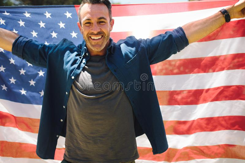 Happy man standing outdoors holding american flag royalty free stock image