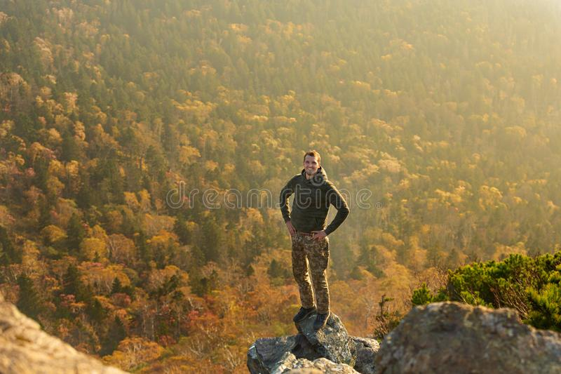 Happy man standing at the top of the mountain. Landscape view of misty autumn mountain hills and man silhouette royalty free stock images