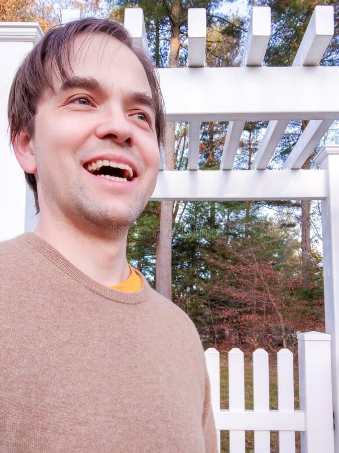 Happy Man steht vor dem weißen Picketzaun am Herbsttag, locker gekleidet, mittelalterlich lizenzfreies stockbild