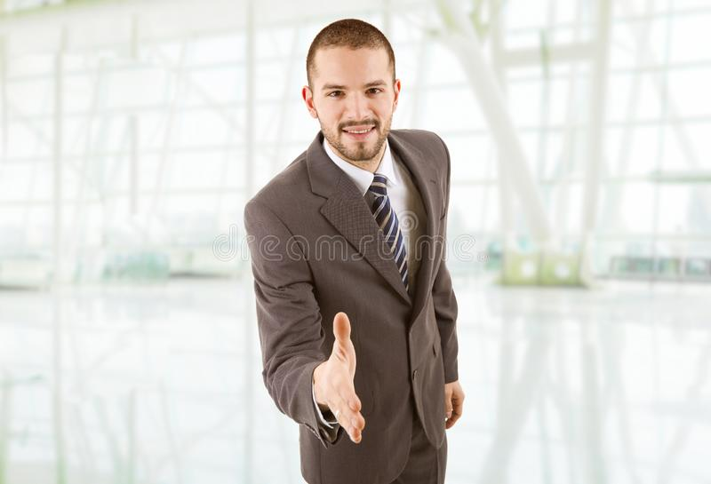 Handshake. Happy man in suit offering to shake the hand, at the office stock image