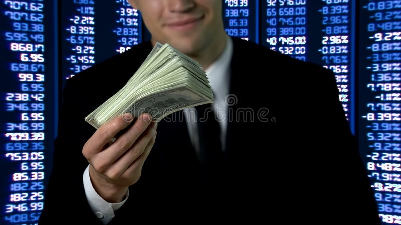 Happy man in suit showing bunch of dollars, financial market data on background. Stock photo stock photo