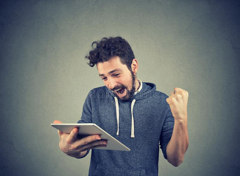Happy man with tablet holding fist up stock photography