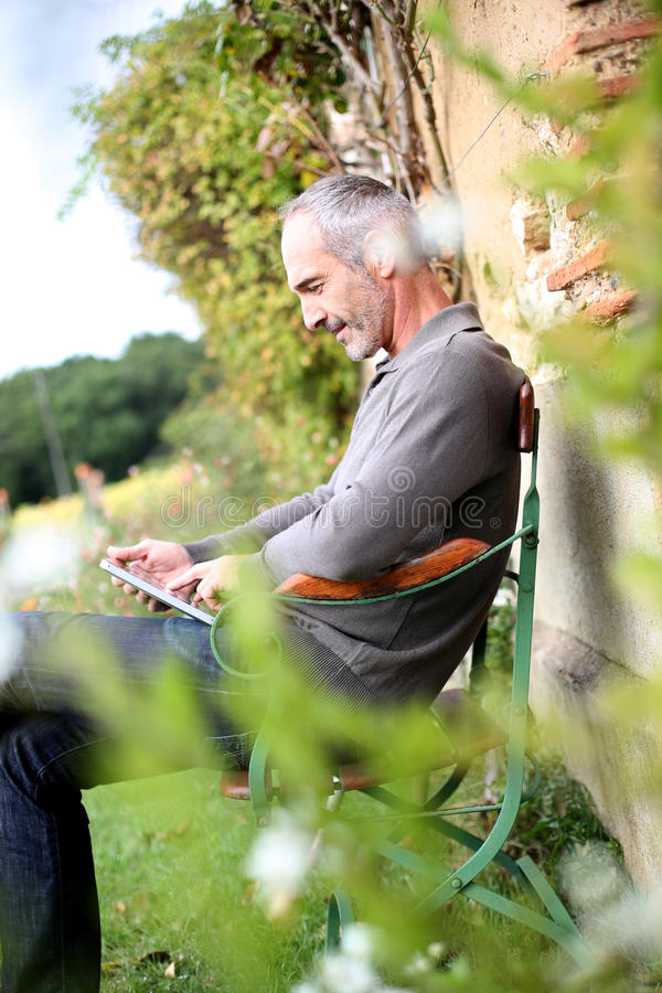 Happy man with a tablet relaxing in garden stock photography