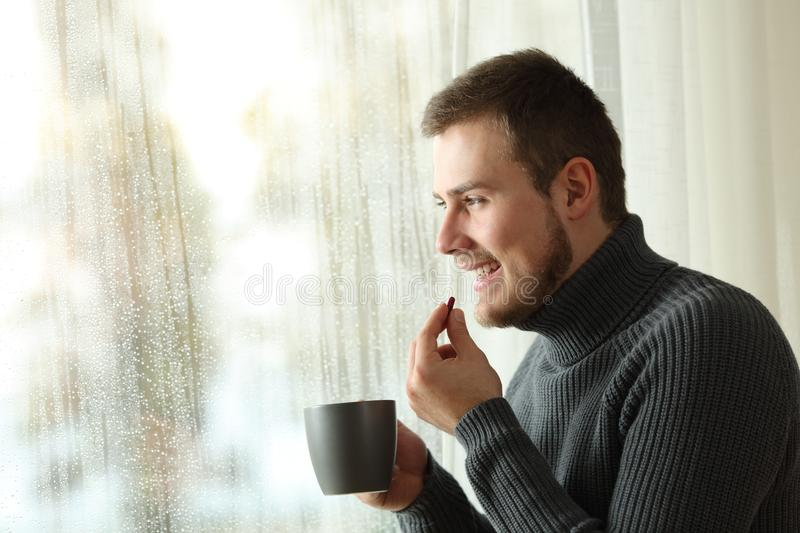 Happy man taking a pill in winter at home. Side view portrait of a happy man taking a pill looking through a window in a rayny day of winter at home royalty free stock photography