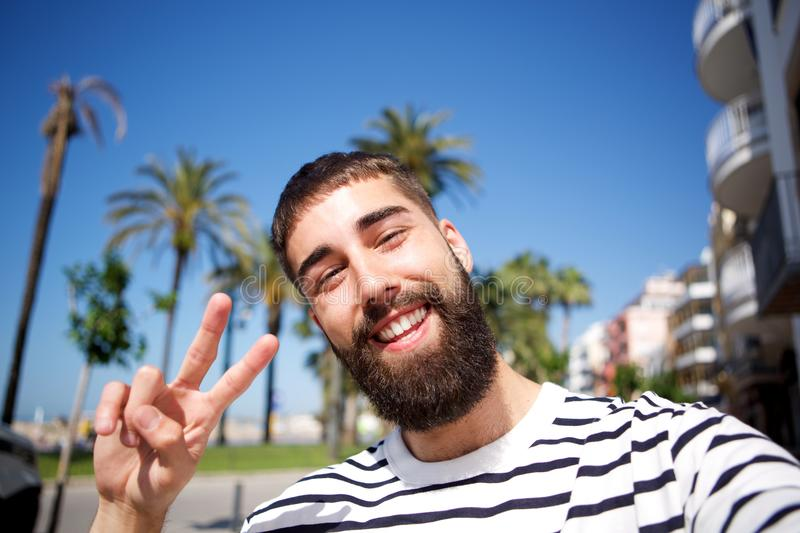 Happy man taking selfie by palm trees. Portrait of happy man taking selfie by palm trees stock photo