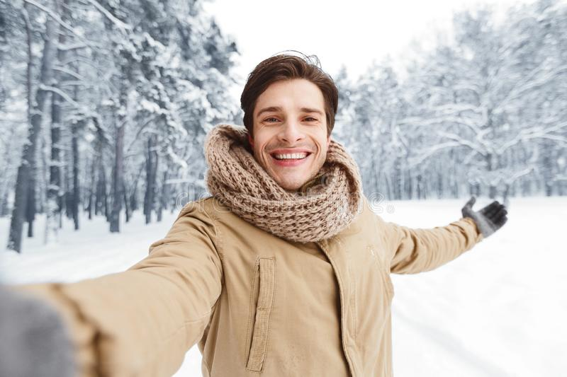 Happy Man Taking Selfie Standing In Winter Forest stock photo