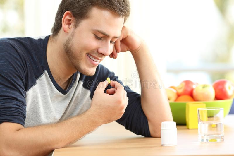 Happy man taking a vitamin pill at home. Happy man taking a yellow omega 3 vitamin pill on a table at home royalty free stock photography