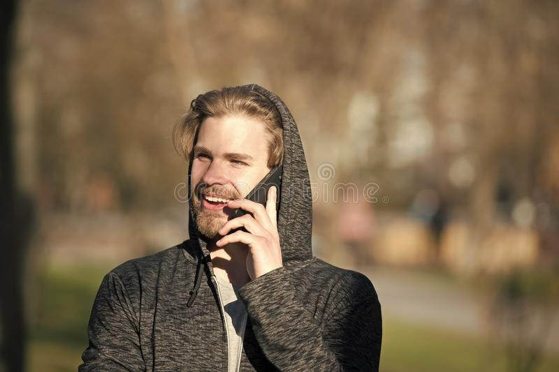Happy man talk on mobile phone in park, communication. Macho in hood with smartphone smile on sunny day, fashion. Modern life, new technology, communication royalty free stock images