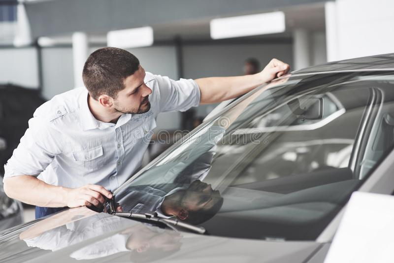 Happy man touching car in auto show or salon. royalty free stock photo