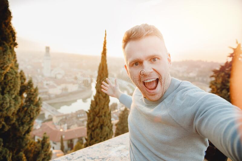 Happy man traveler taking selfie photo on city background Verona Italy sunset. Travel concept stock photos