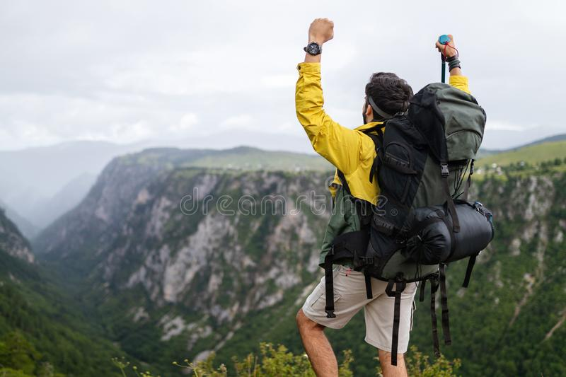 Young man traveling with backpack hiking in mountains royalty free stock images