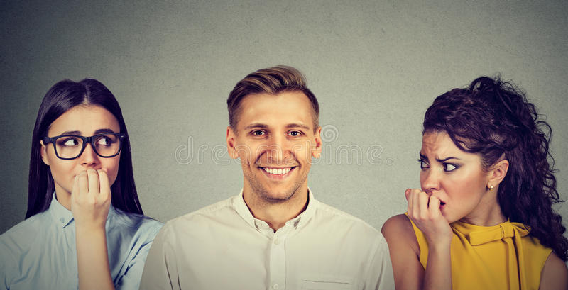 Happy man and two insecure women anxiously looking at him. Happy handsome men and two women anxiously looking at him stock photo