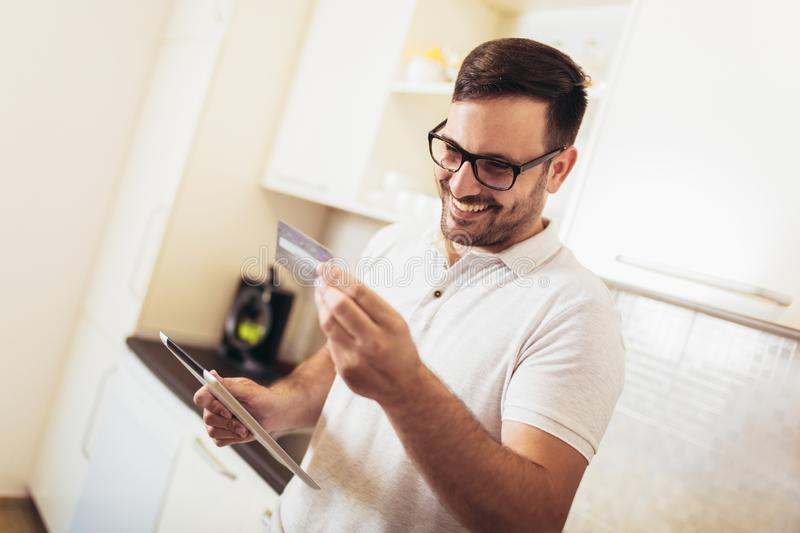 Man using digital tablet and credit card in kitchen at home stock image