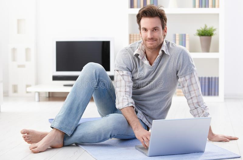 Happy man using laptop at home royalty free stock image