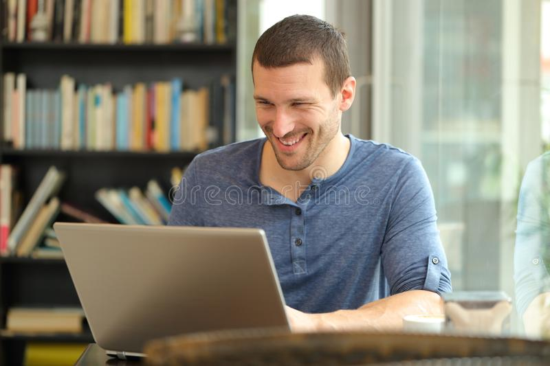 Happy man using a laptop sitting in a coffee shop or home royalty free stock photography