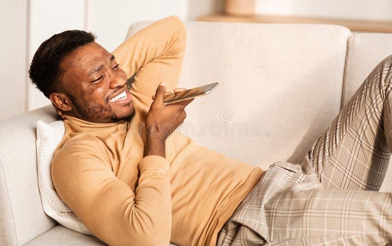 Happy Man Using Phone Loudspeaker Lying On Sofa At Home stock photo