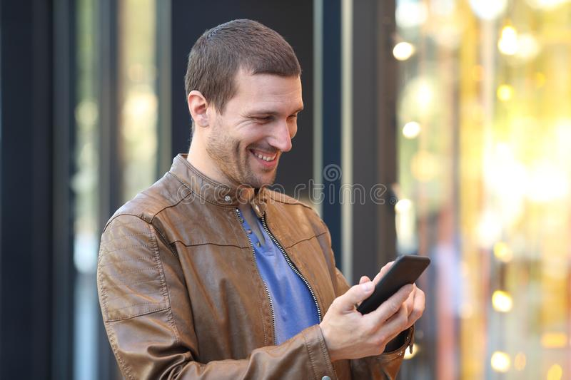 Happy man using phone in a storefront in the street. Happy man using mobile phone in front of a storefront standing in the street stock image