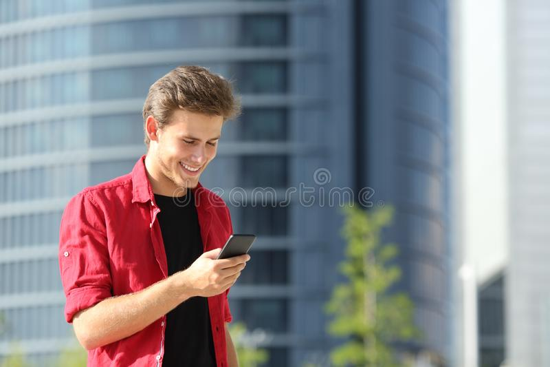 Happy man using a smart phone walking in the street royalty free stock photos