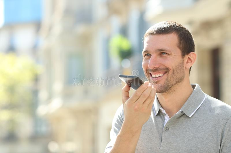 Happy man using voice recognition on phone to send a message. Happy man using voice recognition on mobile phone to send a recorded message in the street royalty free stock photography
