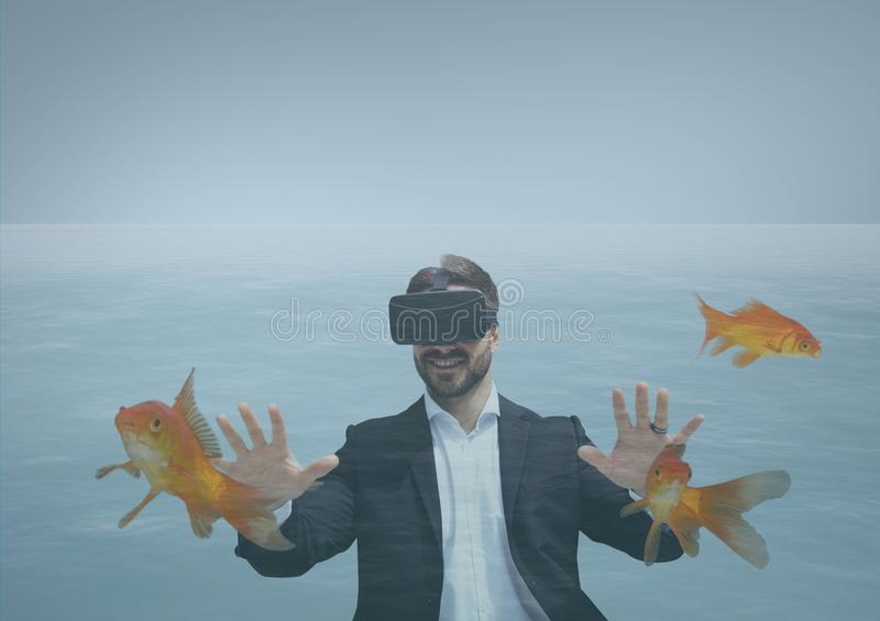 Happy man in VR headset diving with fishes stock photography