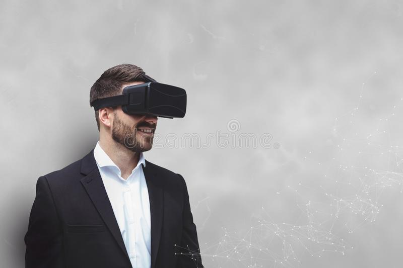 Happy man in VR headset standing against white background stock image