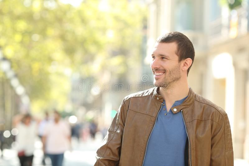 Happy man walking in the street looking at side. Front view of a happy man walking towards camera in the street looking at side stock photography