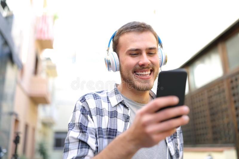 Happy man watching and listening to musinc from smart phone stock photos