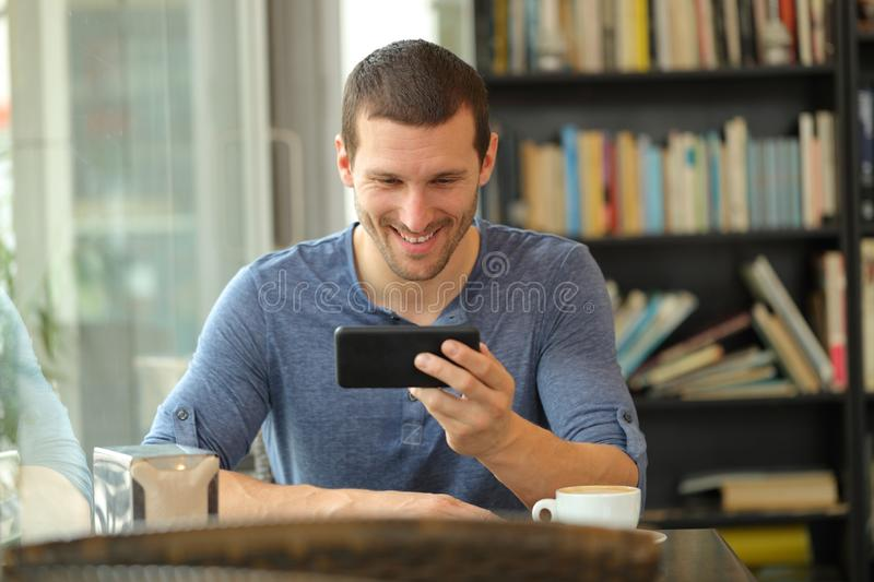 Happy man watching media on smart phone in a bar royalty free stock photos