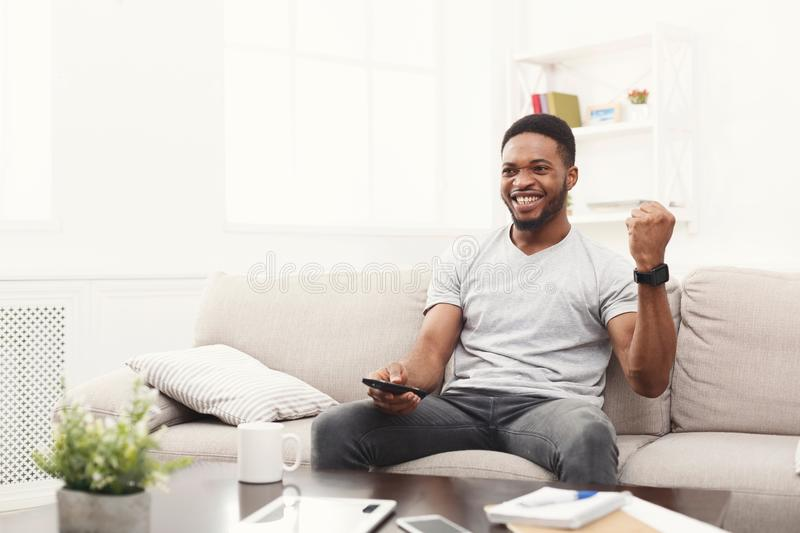 Happy man watching tv using remote controller in living room. Young african-american man watching tv on the couch, happy of favourite football team, pointing royalty free stock photography