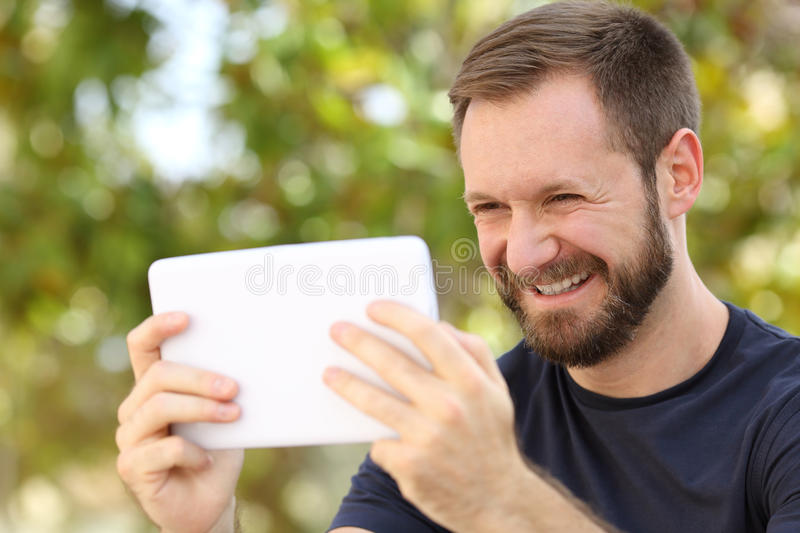 Happy man watching videos in a ereader tablet stock photos