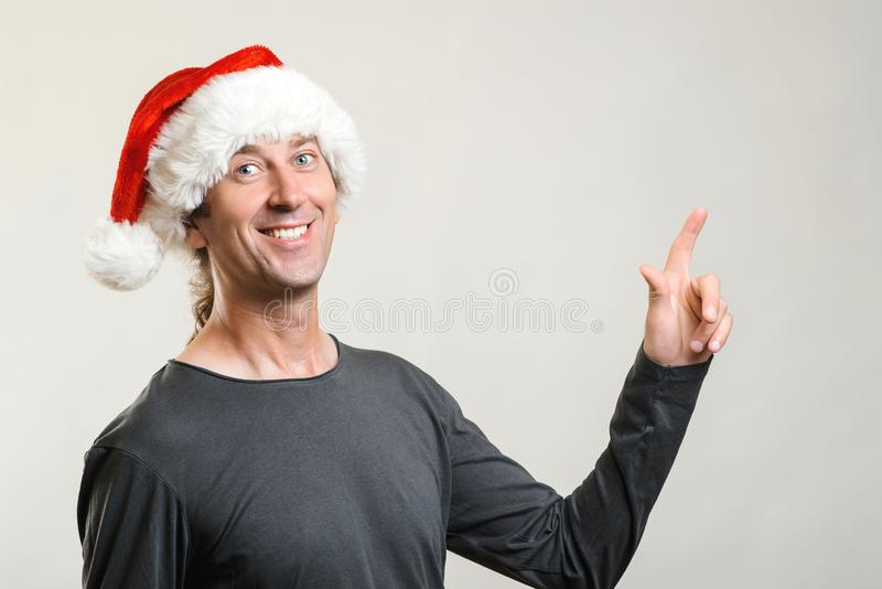 Happy man wearing christmas hat over grey background. Amazed and smiling man while presenting your product and pointing with royalty free stock images