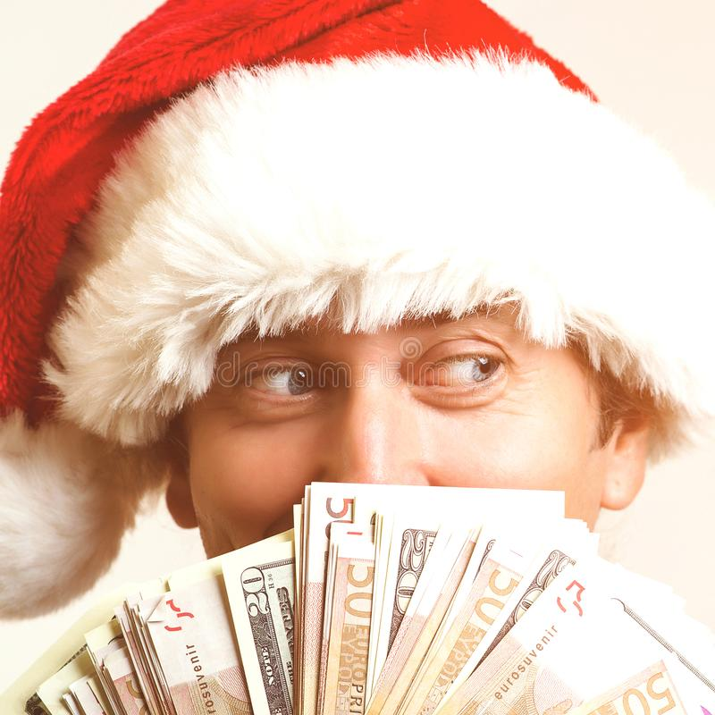 Happy man wearing christmas hat standing isolated over white wall. Looking aside. Santa holding money. Christmas sales, discounts royalty free stock photo