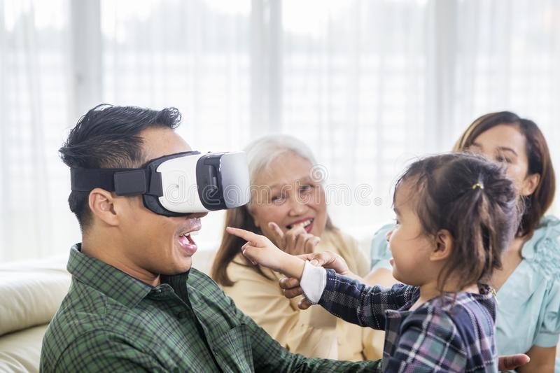 Happy man wears a VR headset with his family. Close up of a happy young men wearing a VR headset with his family at home while sitting on the sofa royalty free stock photo