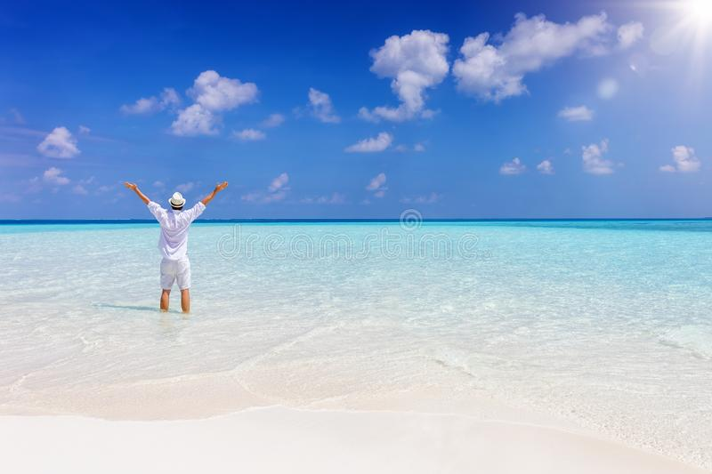 Man stands in turquoise, tropical waters in the Maldives islands, Indian Ocean. A happy man in white summer clothes stands with outstretched arms in turquoise royalty free stock photos