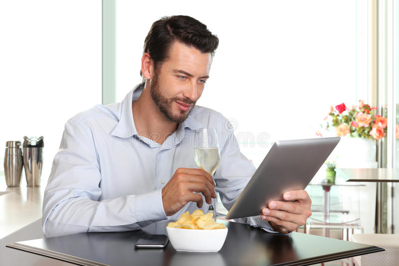 Happy man with wine and tablet at the bar. Happy man with wine and tablet sitting at the bar stock photography