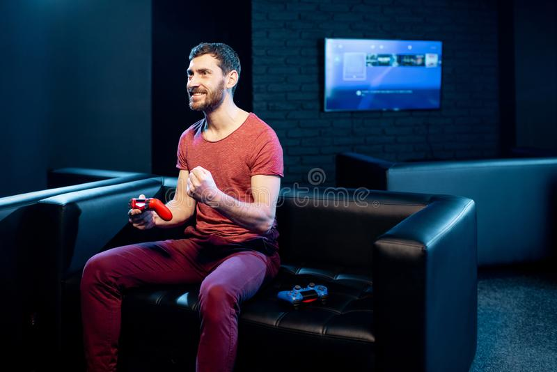 Happy man playing video games with gaming console in the club stock images
