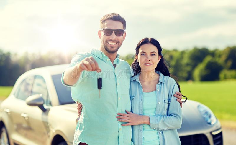 Happy man and woman with car key hugging. Transport, road trip, travel, family and people concept - happy men and women with car key hugging stock photo